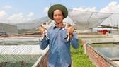 Nguyễn Văn Nữa bên trang trại nuôi ếch của mình