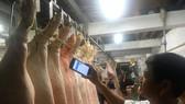 Officials checking pork information at Binh Tan slaughtering house (Photo: SGGP)