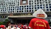 Hàng trăm người mặc đồng phục tập trung trước cổng chợ.