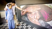 """ Réhahn và bà Xong bên tác phẩm """"Nụ cười ẩn giấu"""" tại buổi ra mắt phòng ảnh nghệ thuật ở TPHCM"""