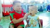 Huỳnh Đình Hạnh (bên trái) đút cơm giúp Lê Hoài Thương trong giờ ăn tại trung tâm