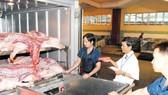 """Hiện nay người dân đang vào cuộc """"giải cứu thịt heo"""". Trong ảnh: Nhân viên thú y kiểm tra thịt heo vận chuyển từ các lò giết mổ trước khi đưa vào chợ"""