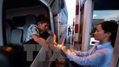Lái xe cố tình chậm chạp trả từng đồng tiền lẻ tại trạm thu phí BOT số 1 quốc lộ 5 huyện Văn Lâm. (Ảnh: Phạm Kiên/TTXVN)