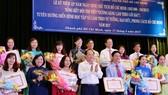 """Phó Bí thư Thường trực Thành ủy TPHCM Tất Thành Cang cùng các đồng chí lãnh đạo TPHCM tuyên dương các tác giả đoạt giải tại hội thi """"Gương sáng làm theo lời Bác"""" Ảnh: VIỆT DŨNG"""