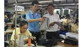 Lê Văn Vũ (bên trái) kiểm tra sản phẩm tại chuyền may