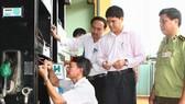 Đoàn liên ngành tỉnh Đắk Lắk thực hiện dán tem trụ bơm xăng dầu ở huyện Cư Mgar. Ảnh: TTXVN