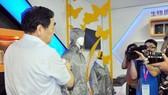 Chủ tịch HĐQT Đường Nhất Lâm tiến hành thí nghiệm về tính dẫn điện của bộ quần áo. Ảnh: TTXVN