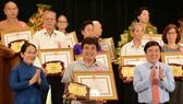 Chủ tịch UBND TPHCM Nguyễn Thành Phong và Phó Bí thư Thành ủy TPHCM Võ Thị Dung chúc mừng các tấm gương thầm lặng mà cao cả. Ảnh: VIỆT DŨNG