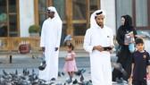 Khách bộ hành đi bên bầy bồ câu ở chợ Souq Waqif, Qatar