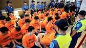 菲律賓全國警察總長羅薩(右)週四和43名穿著橙色上衣的嫌犯,一起出席記者會。(圖源:路透社)