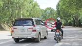 """""""Cò"""" mứt bám theo xe du lịch đưa danh thiếp (khoanh tròn) để đưa tới các cửa hàng kinh doanh đặc sản trên đường Phù Đổng Thiên Vương, TP Đà Lạt. Ảnh: SƠN CƯỜNG"""