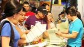 Khách hàng tìm hiểu các tour du lịch tại một hội chợ khuyến mãi ở TPHCM