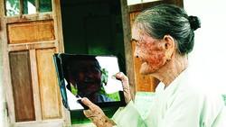 Bà mẹ Việt Nam anh hùng Võ Thị Tới nhìn chân dung mình trong iPad