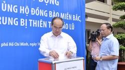 Bí thư Thành ủy TPHCM Nguyễn Thiện Nhân và Phó Bí thư Thường trực Thành ủy TP Tất Thành Cang đóng góp ủng hộ đồng bào vùng lũ. Ảnh: VIỆT DŨNG
