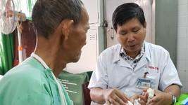 梅仲祥醫生檢查病者手術後的手指舉動狀況。(圖源:黎芳)