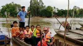 Students in An Giang province go to school on flood season Photo: SGGP