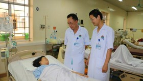 Dr. Phan Thanh Minh visits the pregnant after the operation (Photo: SGGP)