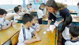 Foreign teacher teach Maths to kids in the program (Photo: SGGP)