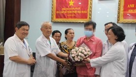 Doctors of Cho Ray present flower to the man on the day he is discharged (Photo: SGGP)