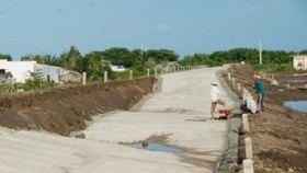Workers are reinforcing eroded dyek due to weak land (Photo: SGGP)
