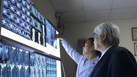 Dr. Vo Ngoc Thien An of the Hospital for Traumatology and Orthopaedics and Dr Vo Van Thanh, a consultant at HCM City's Trung Vuong Hospital, discuss spinal cord dysfunction (Source: VNA)
