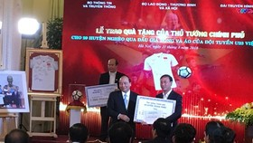 Prime Minister Phuc (L) presents a gift to a leader of poor district (photo: SGGP)