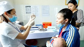 A medical worker prepares to administer vaccine to a baby in the Central Highlands province of Dak Lak (Photo: VNA)