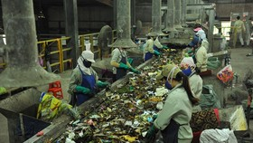 Workers sort waste at a waste treatment factory (Photo: VNA)