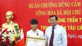 Vice Chairman of the Quang Ngai People's Committee Nguyen Tang Binh (R) presents the Bravery Order to Tran Thanh Ron on November 21 (Photo: VNA)