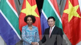 Deputy Prime Minister and Foreign Minister Pham Binh Minh Minh (R) welcomes South Africa's Minister of International Relations and Cooperation Maite Nkoana-Mashabane (Photo: VNA)