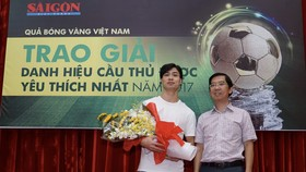 Deputy Editor in chief Nguyen Thanh Loi gives the cup to striker Nguyen Cong Phuong Photo: Hoang Hung