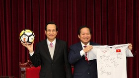 Minister of Labor - Invalids and Social Affairs Dao Ngoc Dung (left) and Minister of Information and Communications Truong Minh Tuan receive ball & football shirt of Vietnam U23 team offered to Prime Minister for auction.