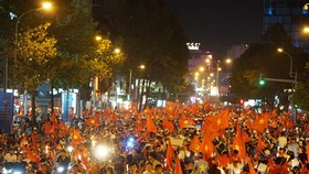 Football fans with national flags, trumpets and drums flock to streets cheering the victory