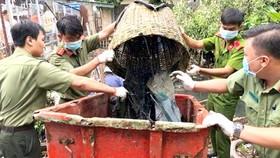 Cán bộ - chiến sĩ trẻ Công an quận 8 tham gia dọn rác trên rạch trong chiến dịch  Hành quân xanh 2018. Ảnh: TUẤN VŨ