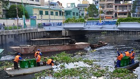 清潔工人正在河涌上打撈垃圾。