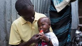 在南蘇丹首都朱巴,28歲的父親尤薩·奧古斯蒂諾(Yosa Augustino)回家後給一歲7個月的孩子吉福特(Gift)餵食高營養花生醬。(圖源:UNICEF))