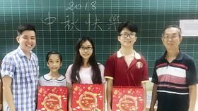 崇華華文中心校政主任徐永華老師(右一)和曾廣健老師向各學生贈送月餅。