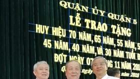 第五郡郡委書記武進仕(左)和郡人委會主席范國輝(右)送花祝賀華人黨員孫盛強。