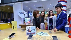 Customers try Mobifone's service. Mobifone's acquisition of 95% of AVG shares will be investigated.  (Photo: VNA)