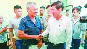 Chairman Nguyen Thanh Phong shakes hands with a residents at a meeting with people relating to Thu Thiem new urban area on October 18 (Photo: SGGP)