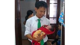 Tài xế Nguyễn Đăng Ngự bên cháu bé mới sinh
