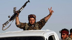 Một chiến binh SDF ăn mừng chiến thắng IS trên đường phố Raqqa. Ảnh: REUTERS