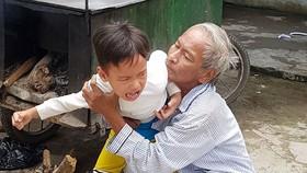 Ông Chinh đang dỗ dành đứa cháu nội  tật nguyền