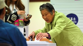 A South Korean elderly woman casts her vote in the presidential election at a polling station in Seoul on Tuesday. — AFP/VNA