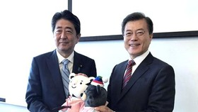 The file photo, taken Sept. 7, 2017, shows South Korean President Moon Jae-in (R) offering the mascots of the 2018 PyeongChang Winter Olympic Games to Japanese Prime Minister Shinzo Abe before the start of their bilateral summit on the sidelines of a regi