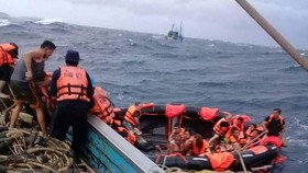 """Rescued tourists are brought aboard a fishing boat, but the Phuket governor's office says """"dozens of Chinese"""" are missing after their tourist boat capsized. (Photo: Phuket Department of Disaster Prevention and Mitigation)"""