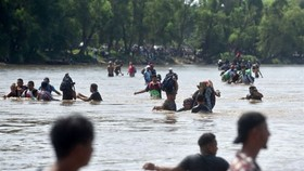 Migrants cross the Suchiate River from Tecun Uman in Guatemala to Ciudad Hidalgo in Mexico. - AFP/VNA Photo