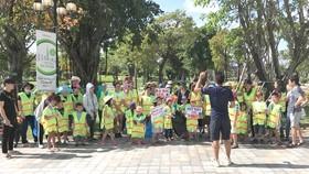 Một đội tình nguyện dọn rác và làm sạch cỏ trong khuôn viên quanh khu chung cư.