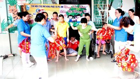 Chi hội Phụ nữ khu phố 10 (phường 4, quận 8, TPHCM) trao quà tặng các em tại Trung tâm Bảo trợ trẻ tàn tật - mồ côi Thị Nghè. Ảnh: MINH THẢO