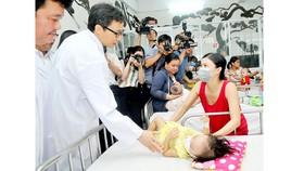 Phó Thủ tướng Vũ Đức Đam thăm hỏi bệnh nhi đang điều trị tại khoa Nhiễm Bệnh viện Nhi đồng 1. Ảnh: THÀNH TRÍ
